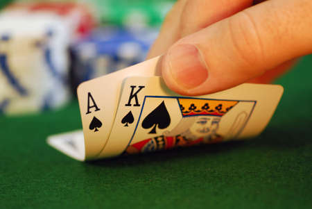 Mans hand lifting up playing cards at a poker table