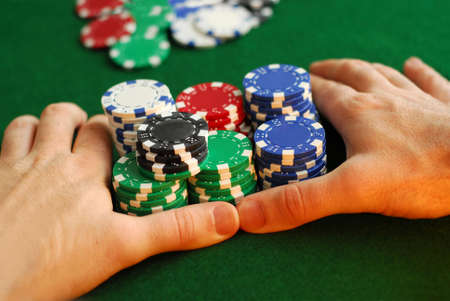Poker player going all in pushing his chips forward photo