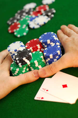 high stakes: Poker player going all in pushing his chips forward Stock Photo