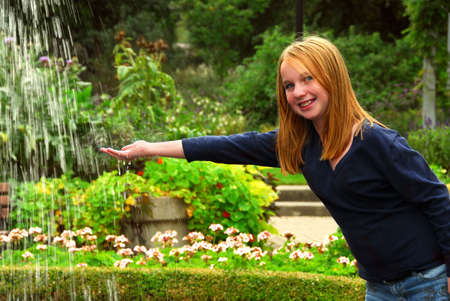 preteen  pure: Young girl holding her hand under falling water in a garden