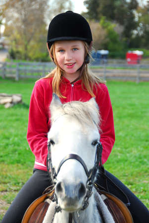 Young girl riding a white pony at countryside photo