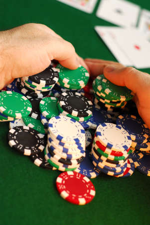 high stakes: Poker player raking a big pile of chips