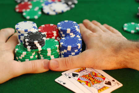 poker game: Poker player going all in pushing his chips forward Editorial