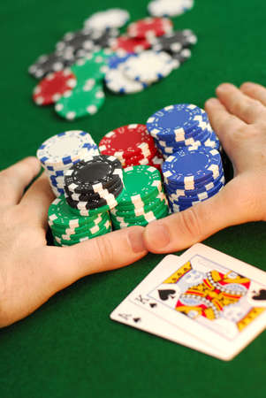 high stakes: Poker player going all in pushing his chips forward Editorial