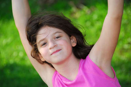 Portrait of a young girl playing on a playground at summertime photo