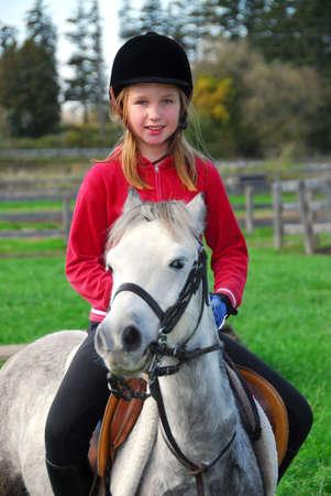 Jong meisje rijdt op een witte pony op platteland