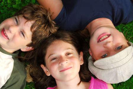 ni�as sonriendo: Retrato de tres ni�os peque�os acostados en la hierba buscar