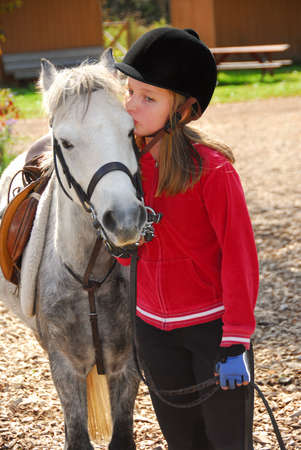 Portrait of a young girl with a white pony photo