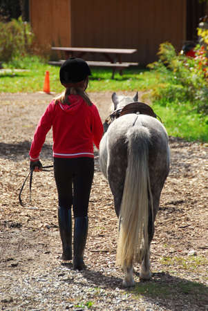 Young girl leading her pony back to the stable