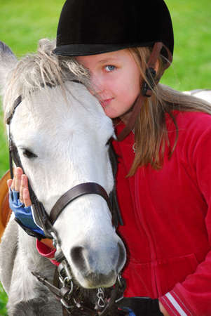 pony girl: Portrait of a young girl with a white pony Stock Photo