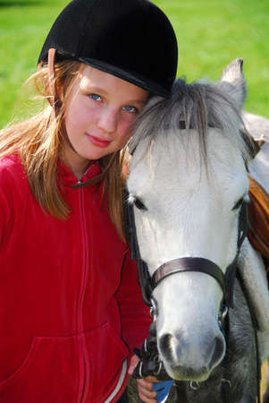 country girls: Portrait of a young girl with a white pony Stock Photo