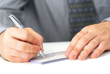Closeup of mans hands writing a cheque photo