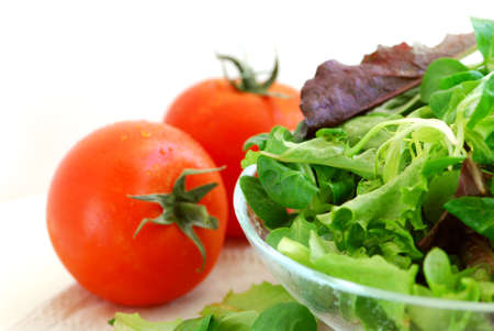 Fresh  greens salad and tomatoes on white background