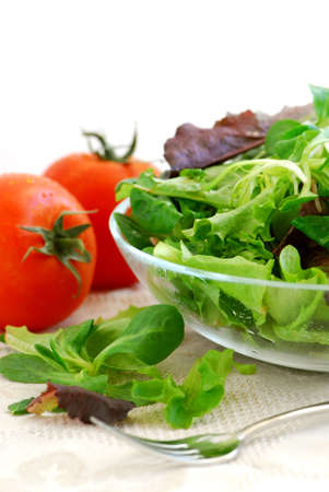 the greens: Fresh  greens salad and tomatoes on white background