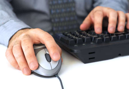 Closeup of mans hands with computer mouse and keyboard photo