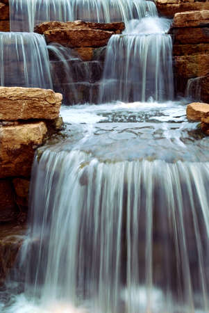 Beautiful cascading waterfall over natural rocks, landscaping element photo