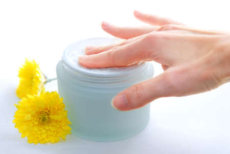 Womans hand touching a creame in open jar