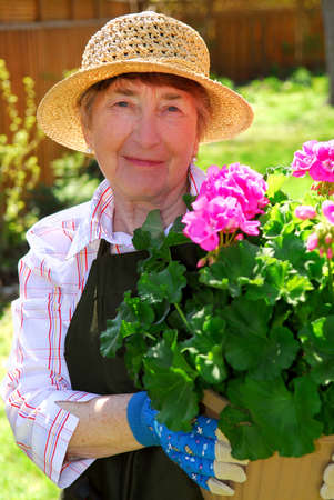 old people: Attractive senior woman holding a pot with flowers in her garden Stock Photo