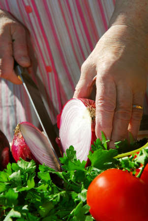 Hands of an elderly woman cooking with fresh vegetables photo