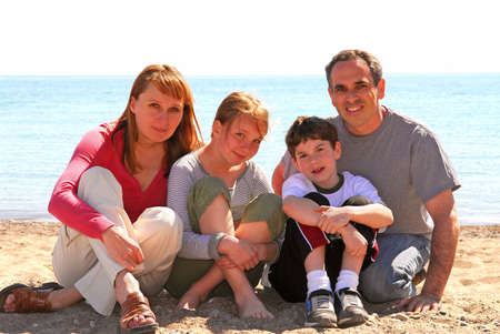 Portrait of a happy family of four sitting on a sandy beach