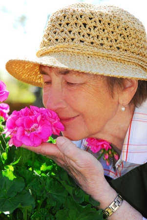 Portrait of a happy senior woman in her garden smelling flowers photo