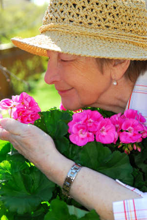 Portrait of a happy senior woman in her garden smelling flowers Stock Photo - 928226