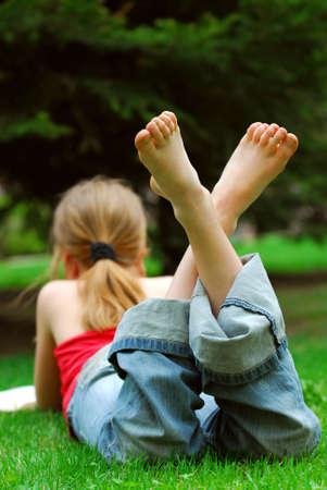 Niña relajante con un libro sobre la hierba verde en un parque de verano Foto de archivo - 928229