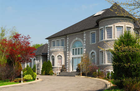 mansion: Front of a large beautiful executive home under blue sky