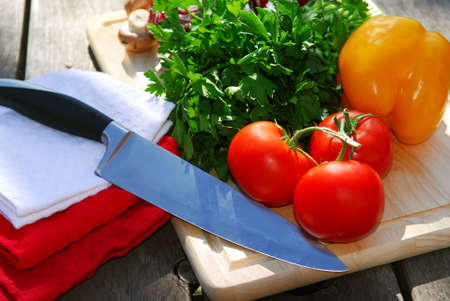 Assorted fresh vegetables on cutting board on rustic table with a chef knife photo
