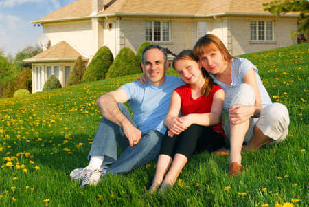 Portrait of a happy family of three on the lawn on front of their house photo