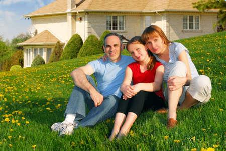 fachada de casa: Retrato de una familia feliz de tres en el jard�n de enfrente de su casa