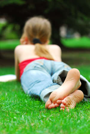 Young girl relaxing with a book on green grass in a summer park Archivio Fotografico
