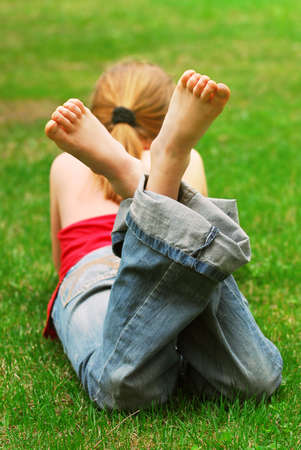 feet crossed: Young girl relaxing with a book on green grass in a summer park Stock Photo