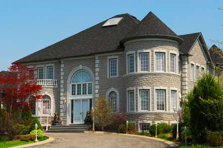 affluence: Exterior of a  large beautiful executive home under blue sky