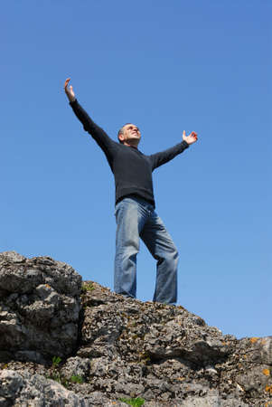 arm up: A man standing on a cliff with his arms raised to the blue sky Stock Photo