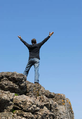 arms wide: A man standing on a cliff with his arms raised to the blue sky Stock Photo