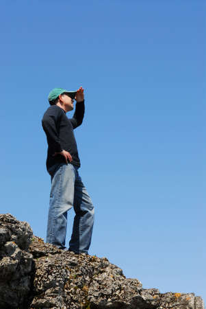 A man standing on top of a cliff looking into the distance photo