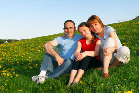 Portrait of a happy family of three on blooming summermedow photo