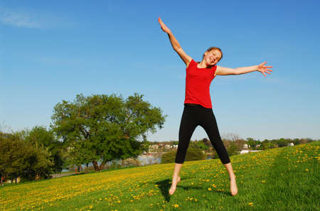 Happy young girl jumping on green field photo