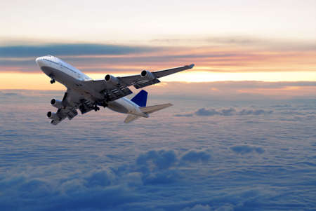 airplanes: Big passenger airplane flying above the clouds and sunset