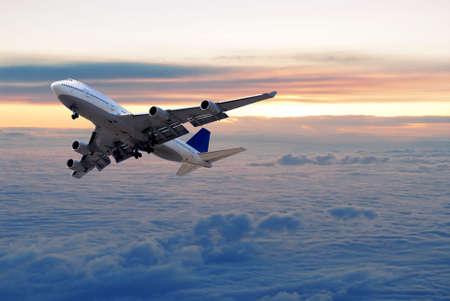 Big passagier vliegtuig vliegt boven de wolken en zonsondergang