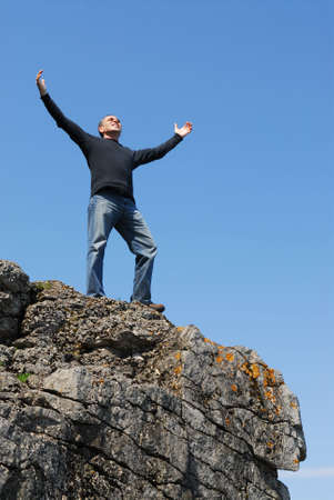 top: A man standing on a cliff with his arms raised to the blue sky Stock Photo