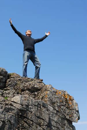 Un homme se tenant sur une falaise avec ses bras a augmenté au ciel bleu Banque d'images - 950411