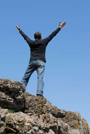 A man standing on a cliff with his arms raised to the blue sky