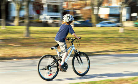 panning: Panning shot of a boy riding a bicycle, motion blurred background