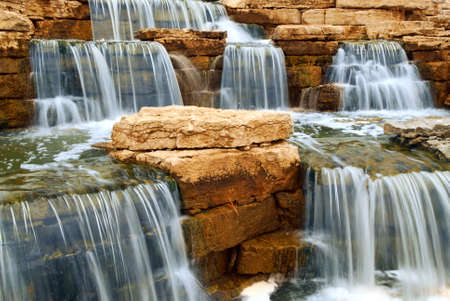 cascading: Beautiful cascading waterfall over natural rocks, landscaping element