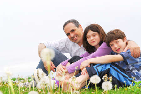 Portrait of a happy family of three on green grass photo