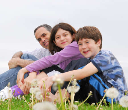 Portrait of a happy family of three on green grass Stock Photo - 958272