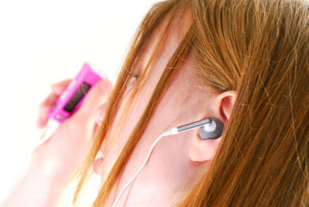 dance preteen: Young teendage girl listening to music on her mp3 player Stock Photo