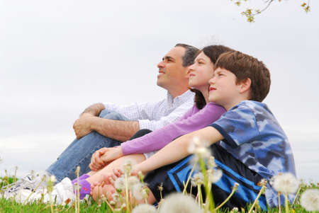 profile: Portrait of a family father and children outside on green grass